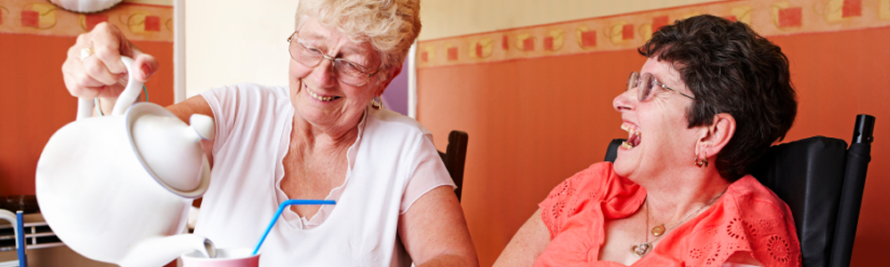 Carers Support photo of a woman pouring tea and another woman laughing