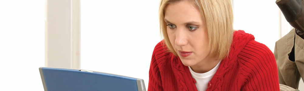 A woman in a red jumper looking at a laptop screen