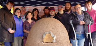 Tenants and Gorwing Together members pose for a photo with their new cob oven