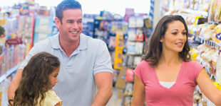 A couple and their child in a supermarket food shopping